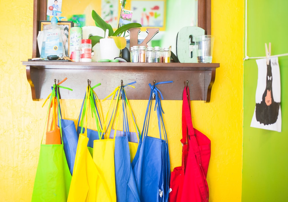assorted-color bag lot hanging on brown wooden wall rack