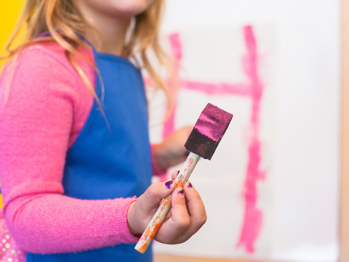 girl using pink paint brush