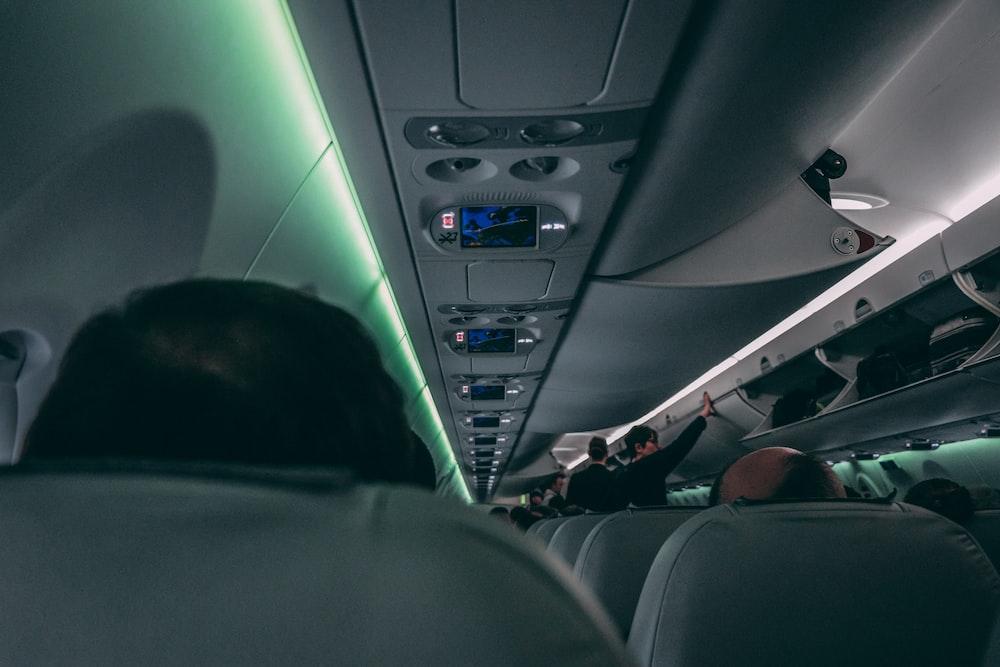 people sitting on passenger plane seats while flight attendants standing on aisle inside plane