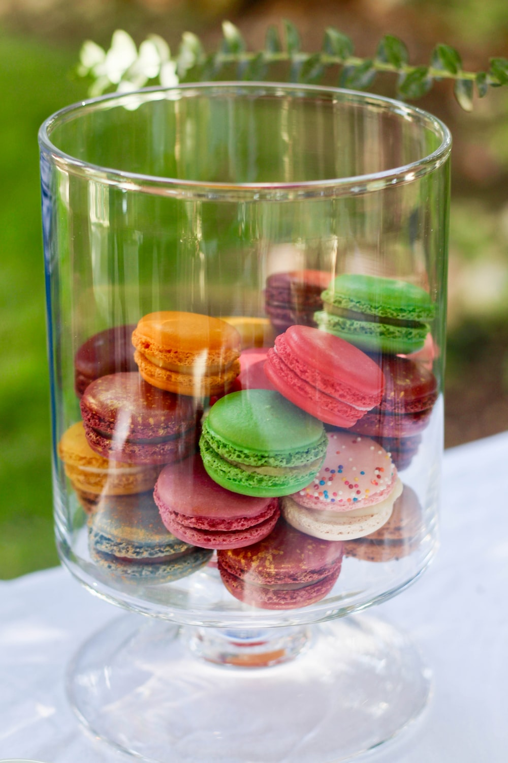 French macaroons inside clear glass container on top of table