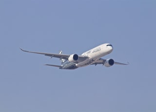 white airplane taking off during daytime