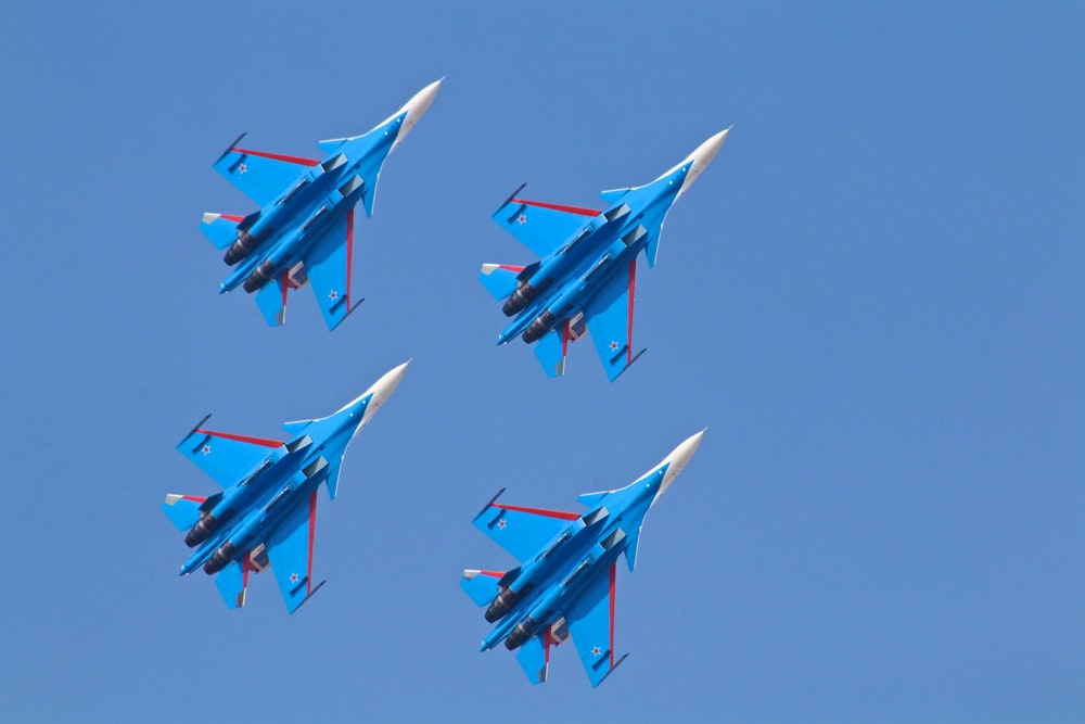 four blue fighter planes under blue sky