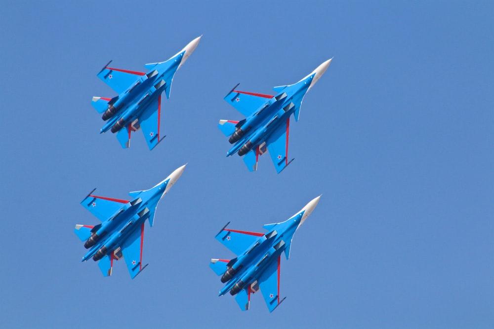 four blue fighter planes under blue sky