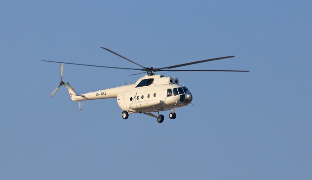 white helicopter under blue sky during daytime
