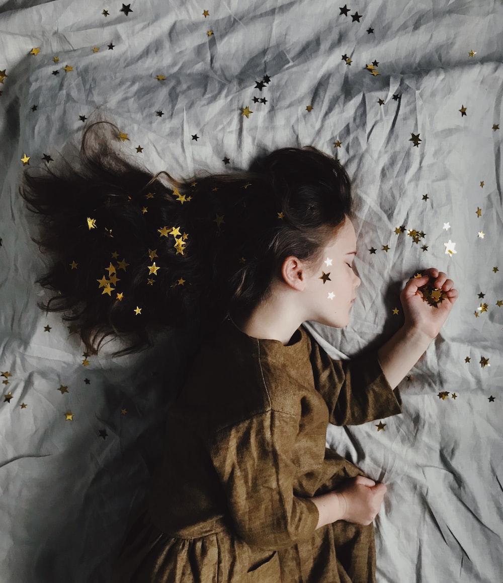 woman in brown long-sleeved top sleeping on bed