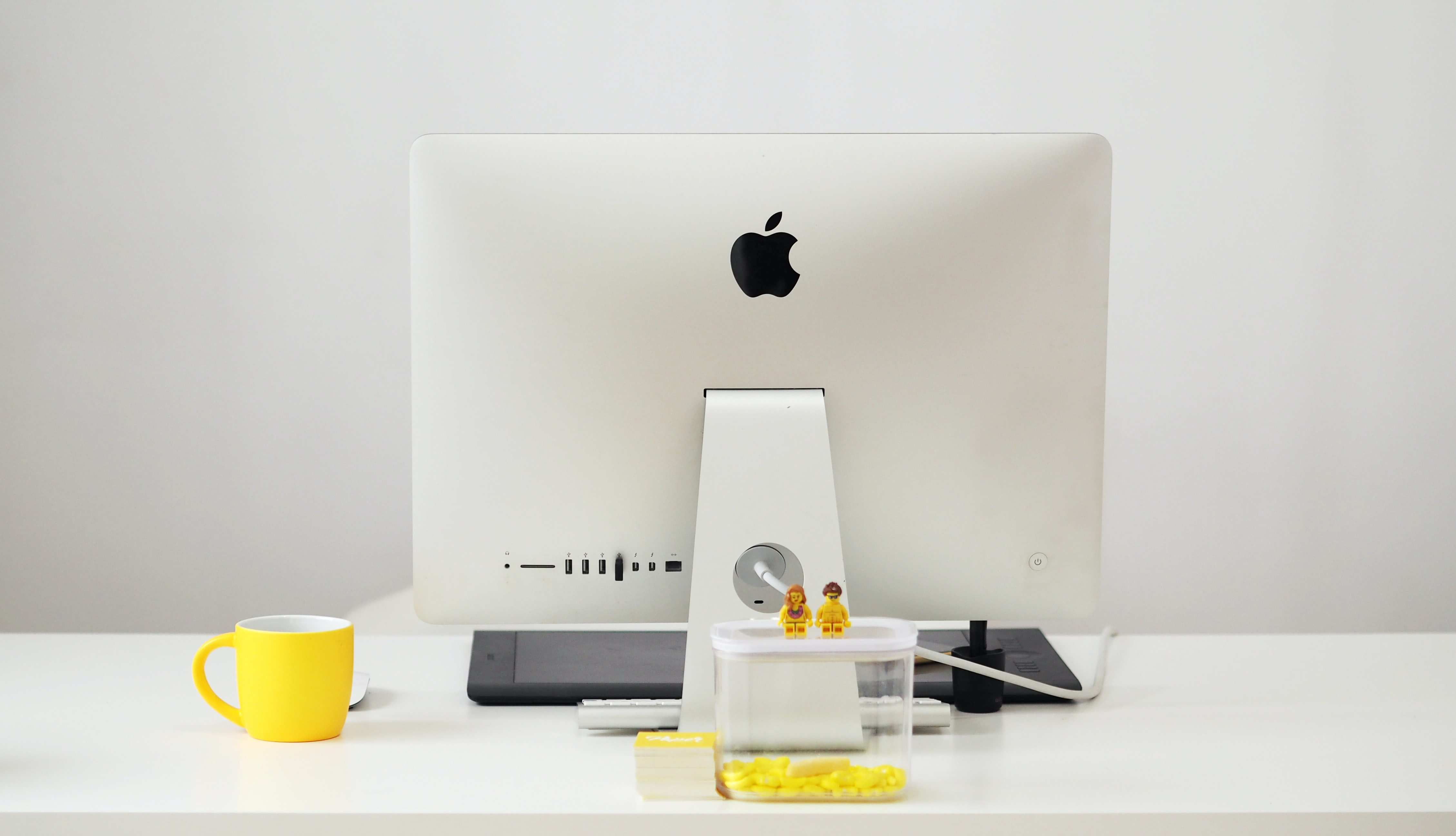 silver iMac beside yellow mug