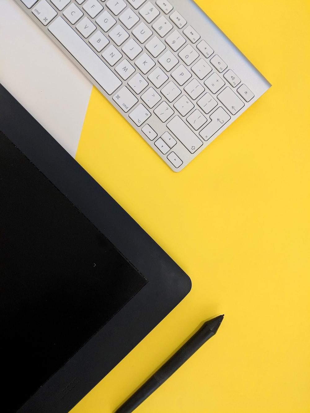 gray Apple wireless keyboard beside black tablet computer and stylus pen