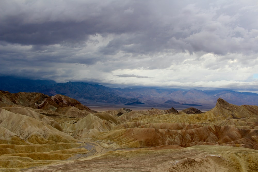 beige mountains under cloudy sky during daytime