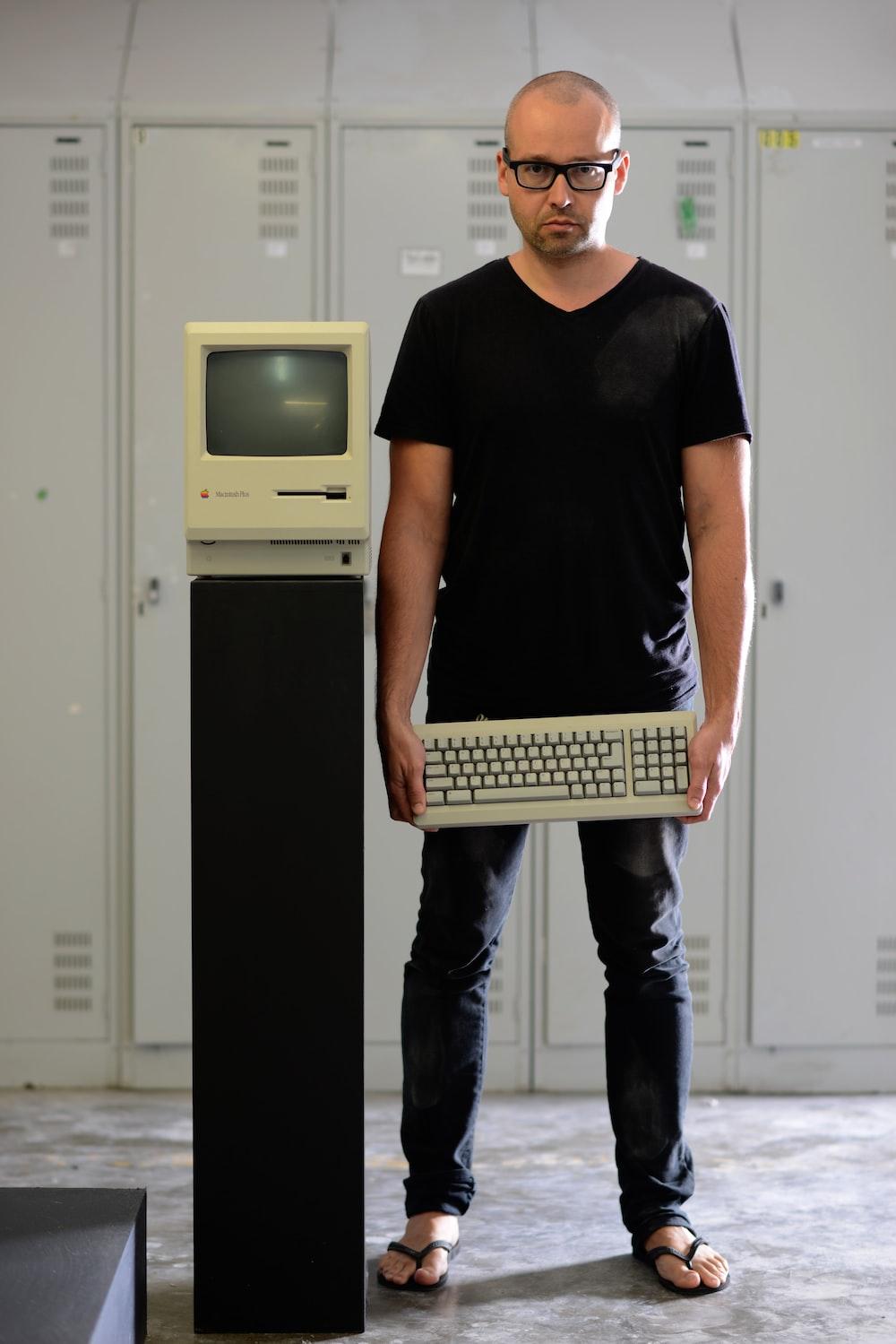 man in black shirt holding computer keyboard