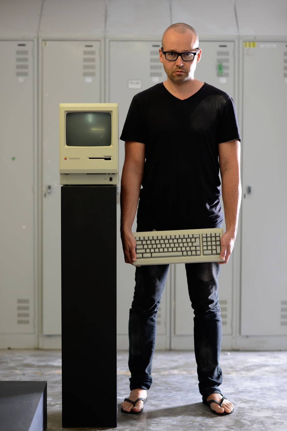 man in black shirt holding computer keyboard