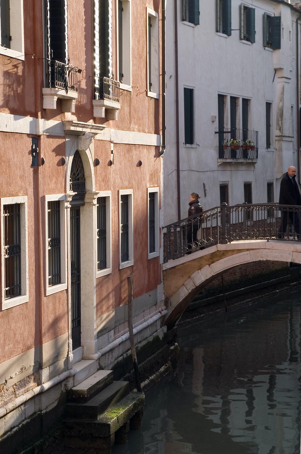woman walking in bridge beside brown concrete building