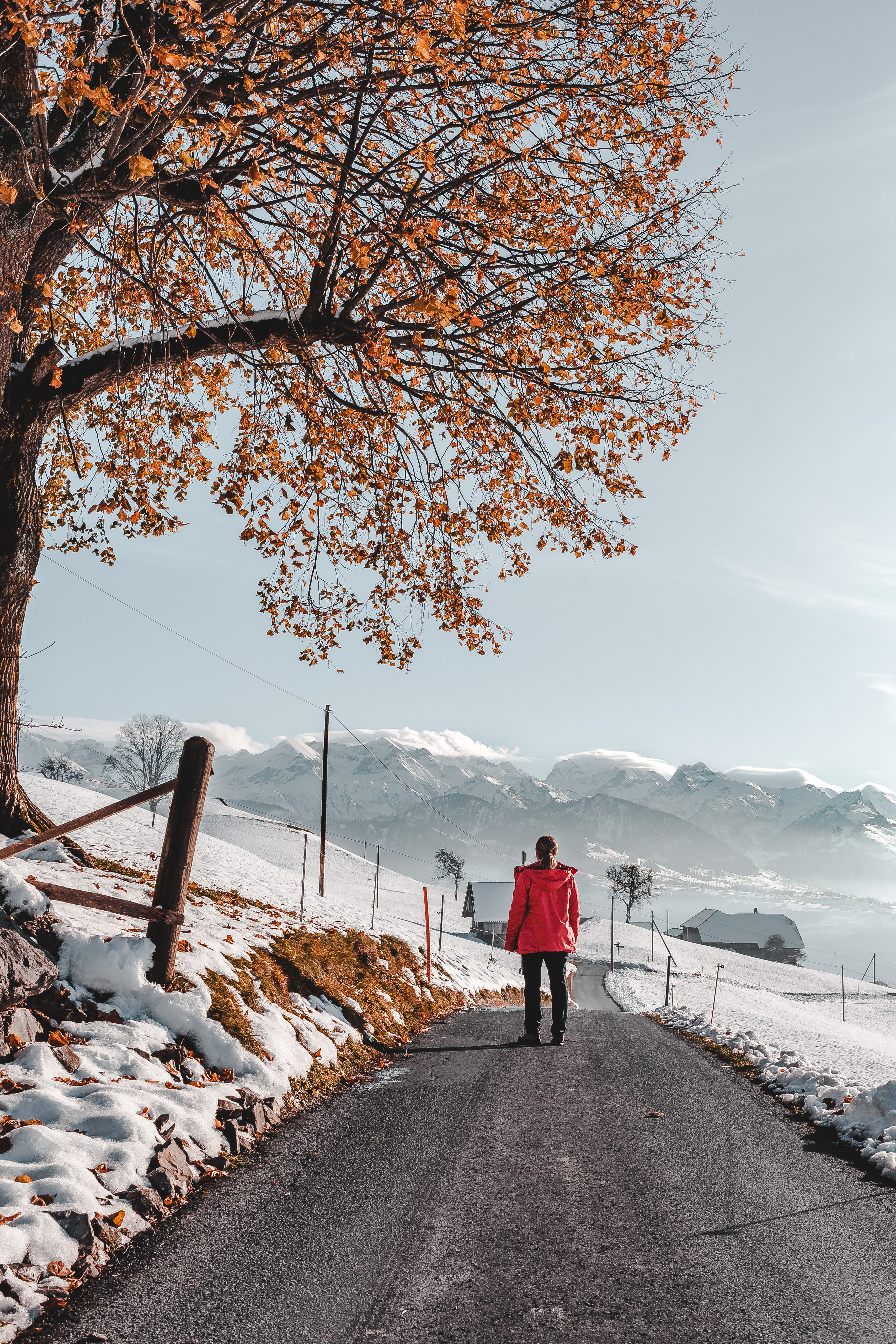 photo of person walking on road wearing red jacket