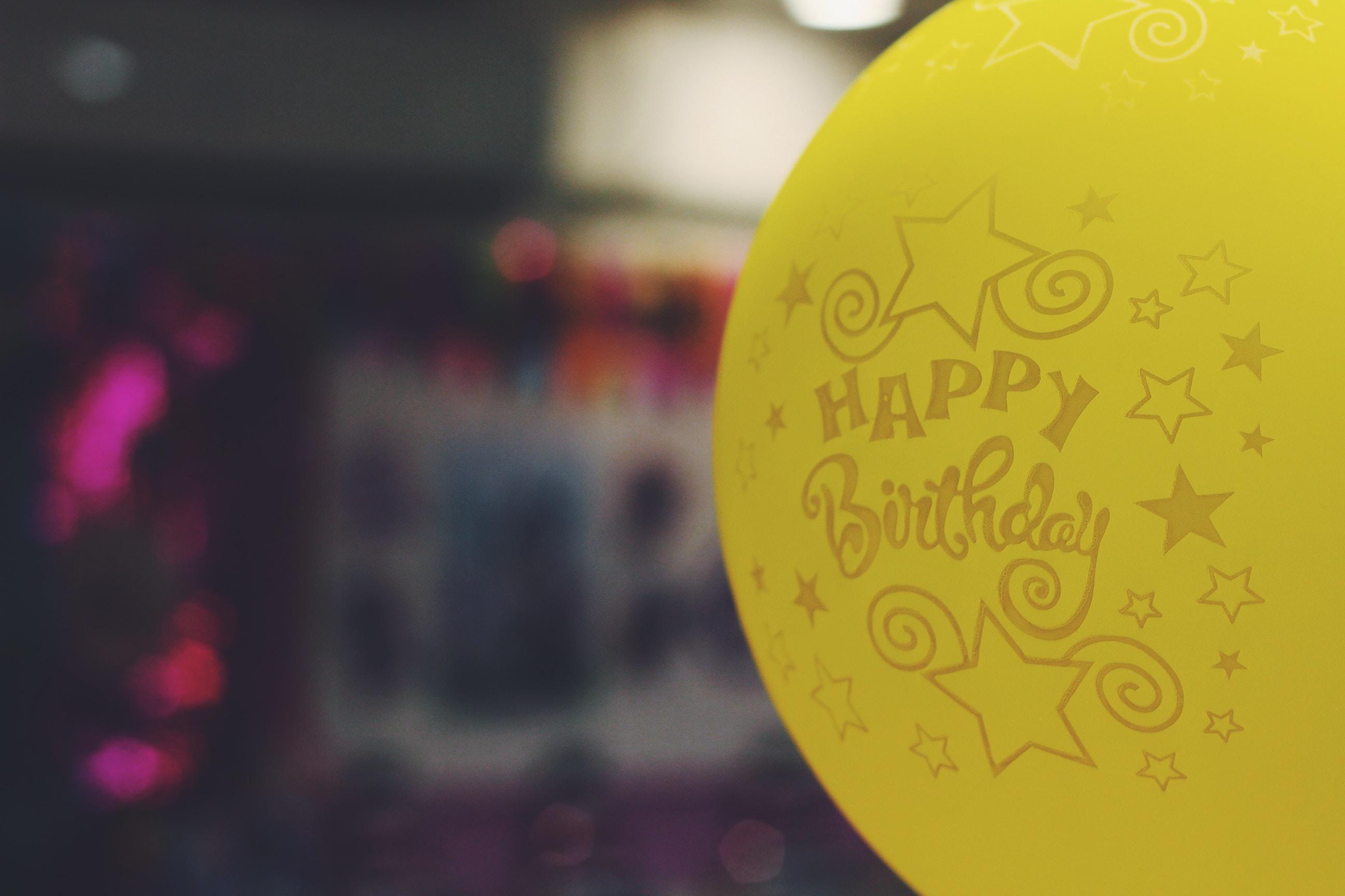 shallow focus photography of yellow happy birthday-printed balloon