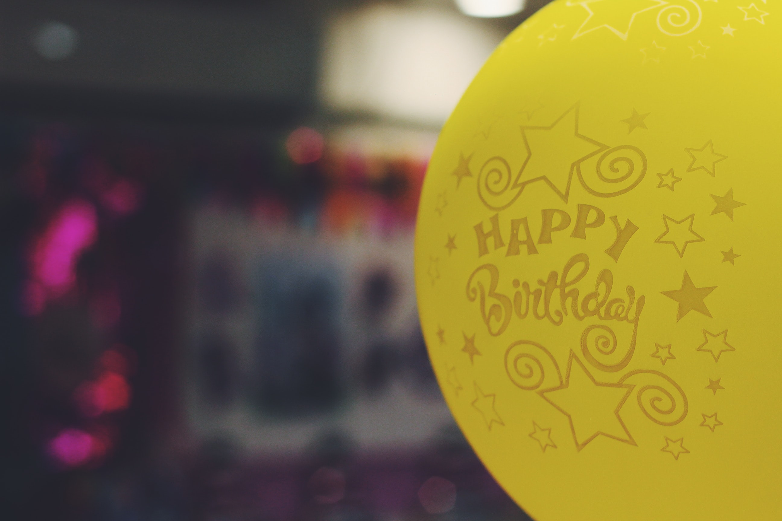 shallow focus photography of yellow happy birthday-printed balloon