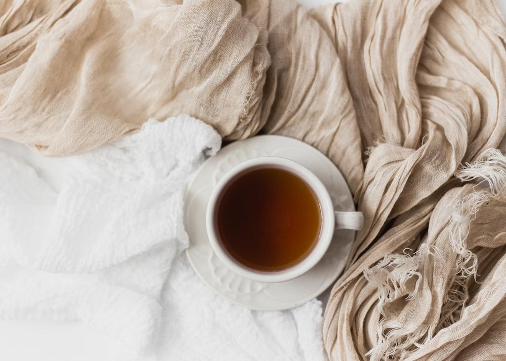 tea filled white ceramic mug on white ceramic saucer