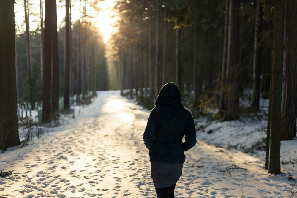 woman walking on snowfield pathway