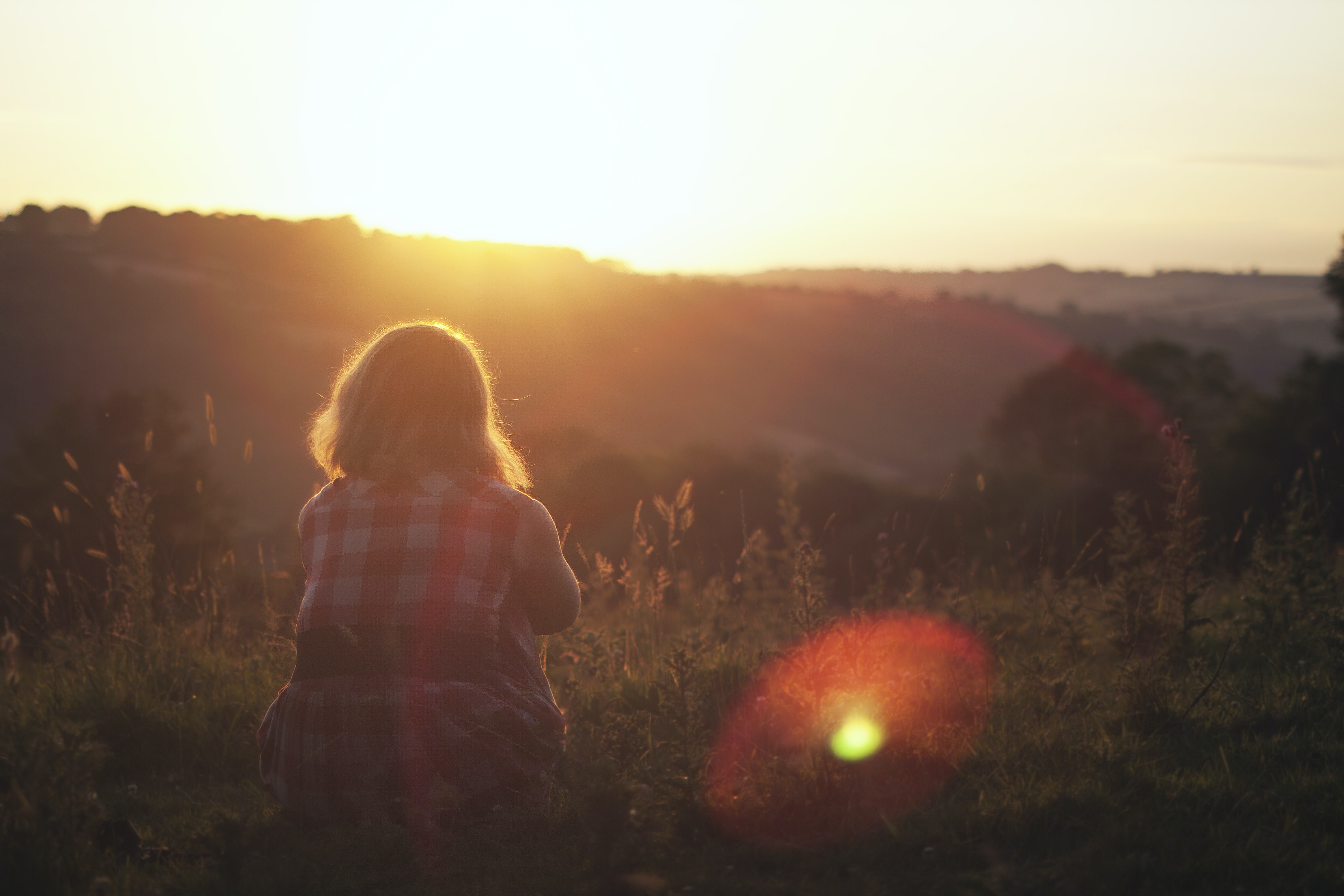 woman sitting on green grass while watching sunset