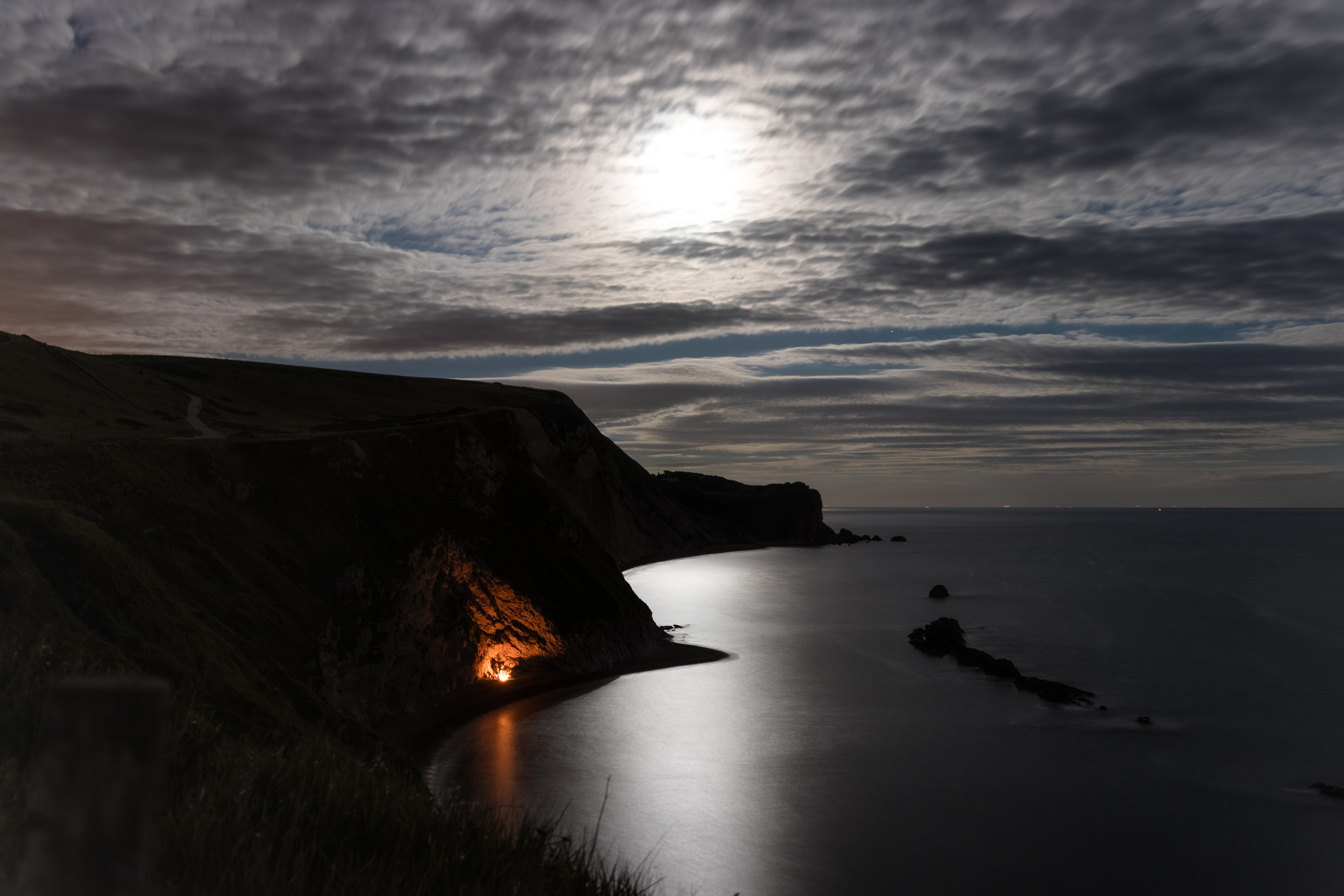landscape photography of cliff under gray sky at nighttime