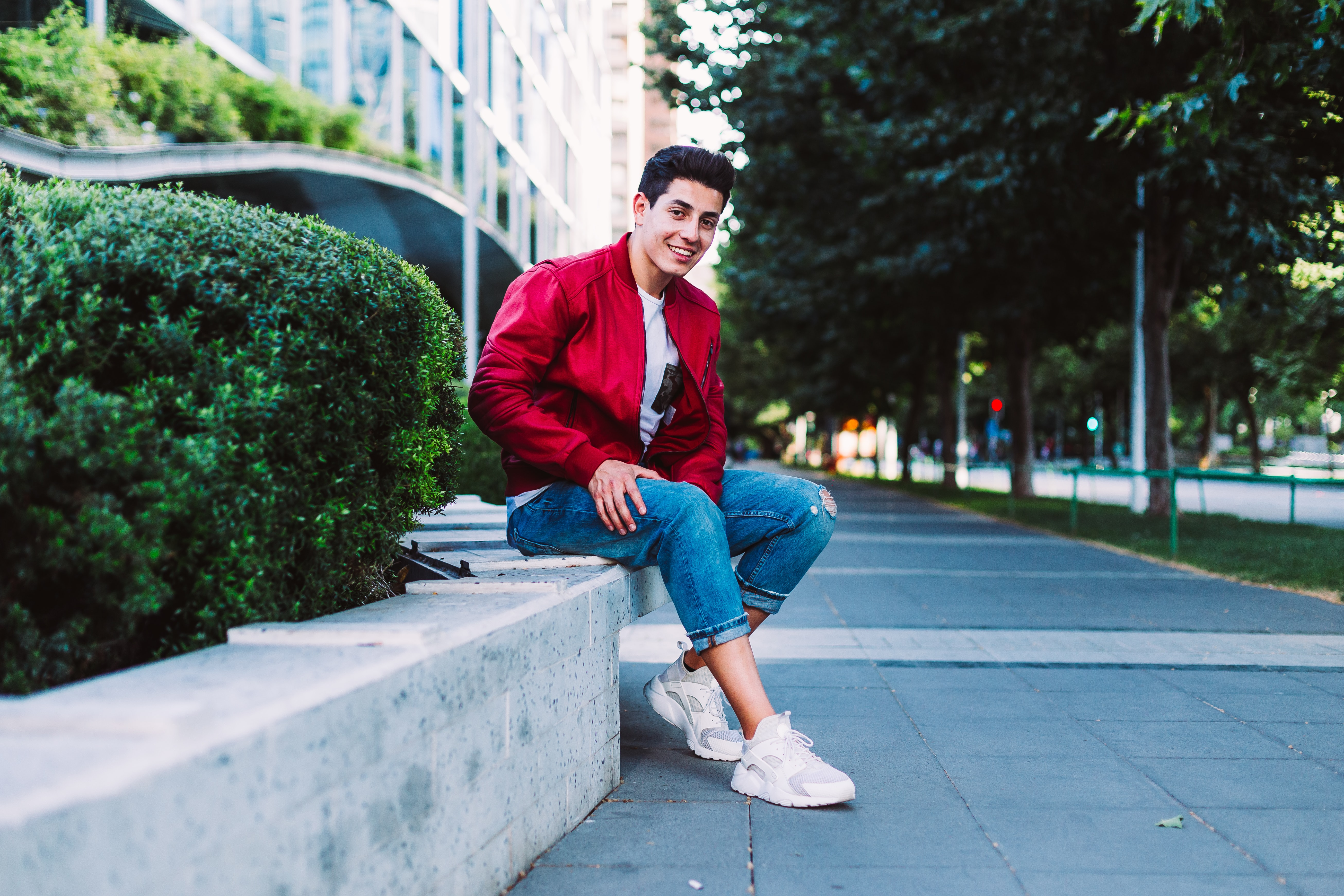 shallow focus photography of man sitting on pavement while smiling