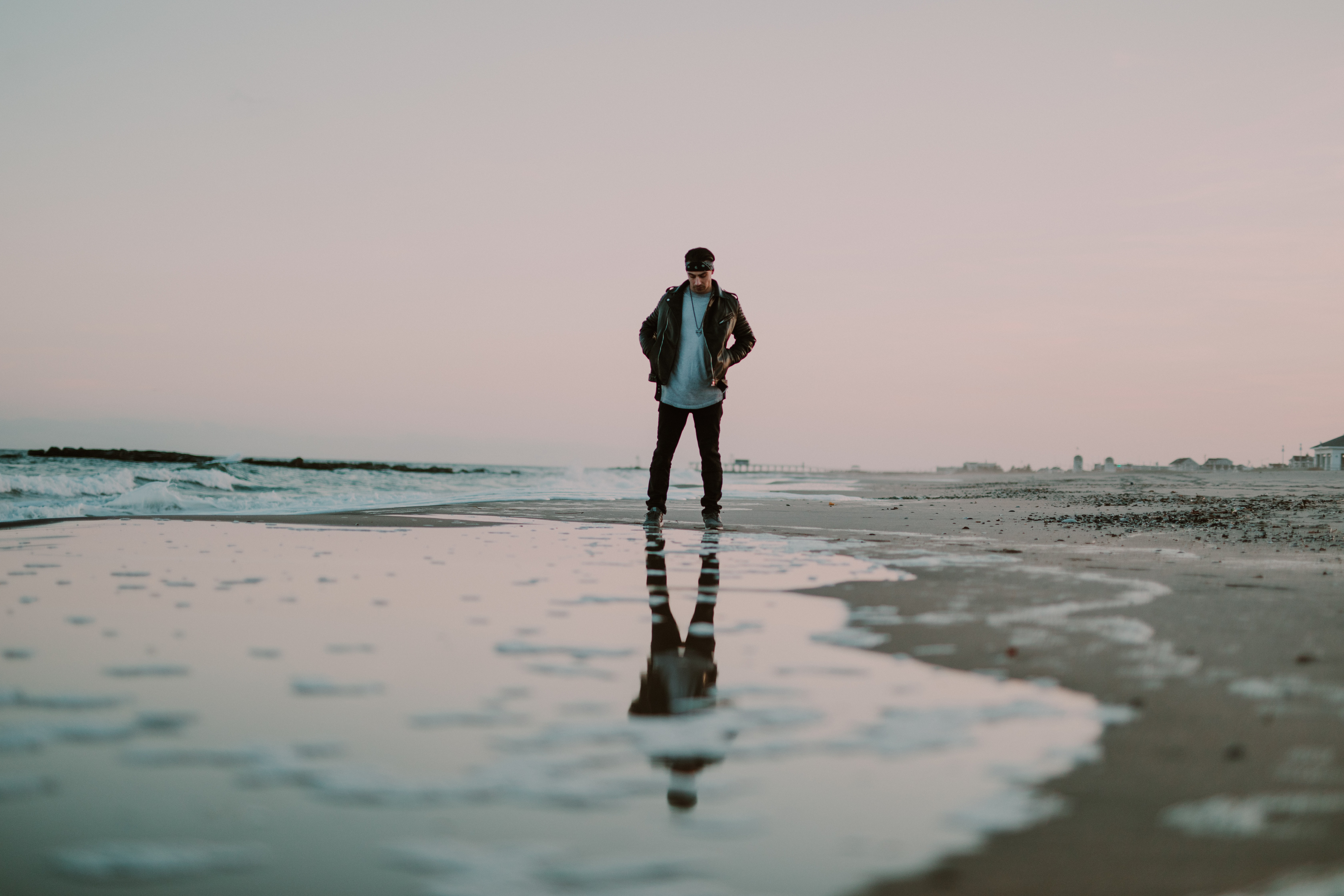 photography of man standing near water body