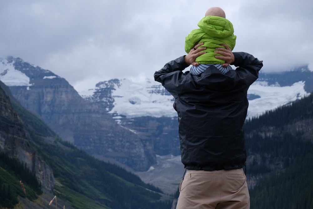 person carrying baby on his neck overlooking mountain