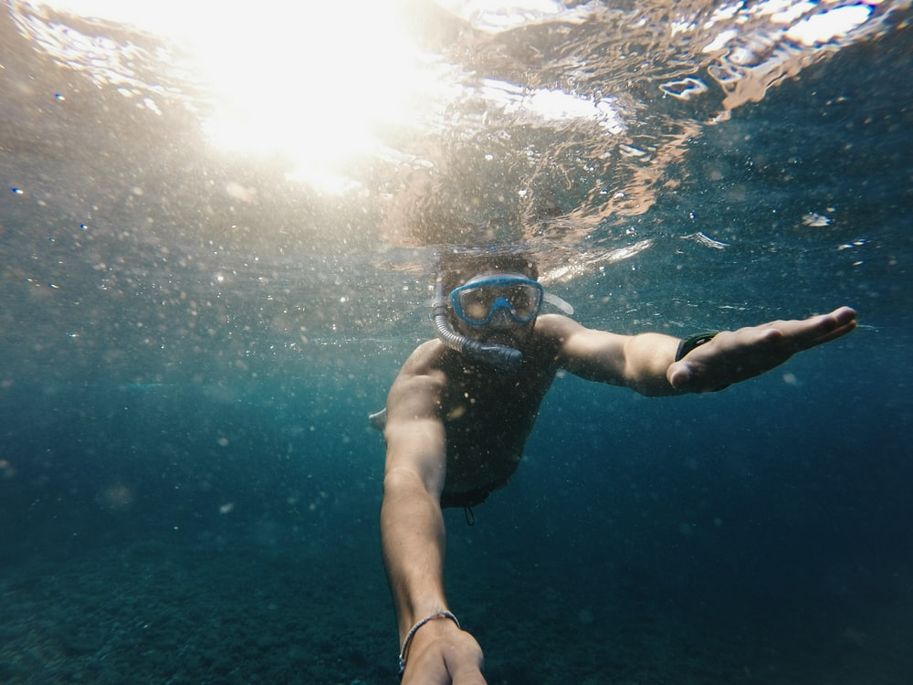 man swimming underwater with goggles
