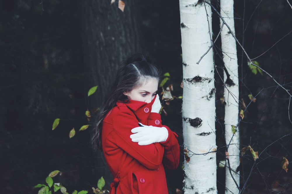 close-up photography of woman covering mouth by red apparel