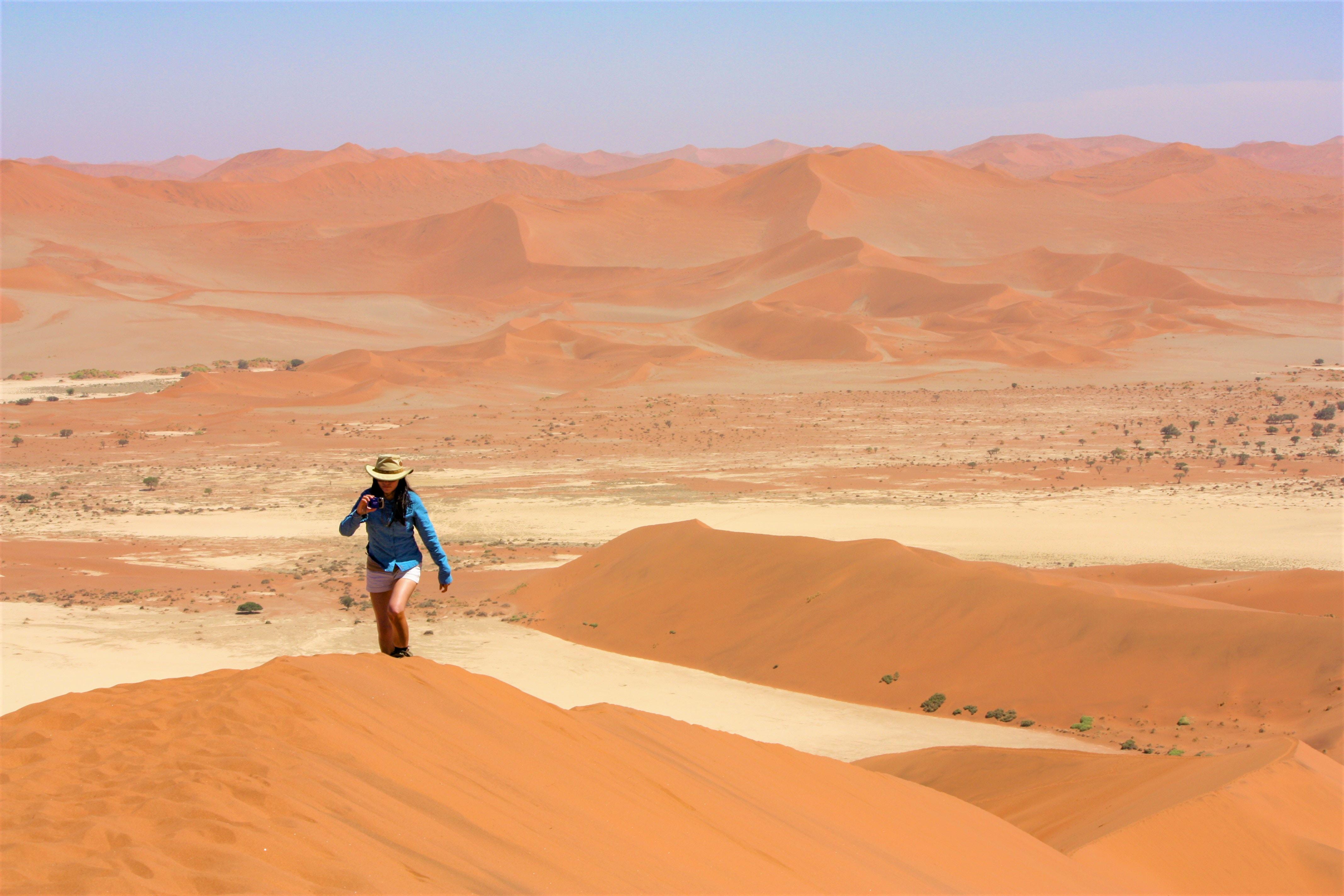 woman walking uphill in desert