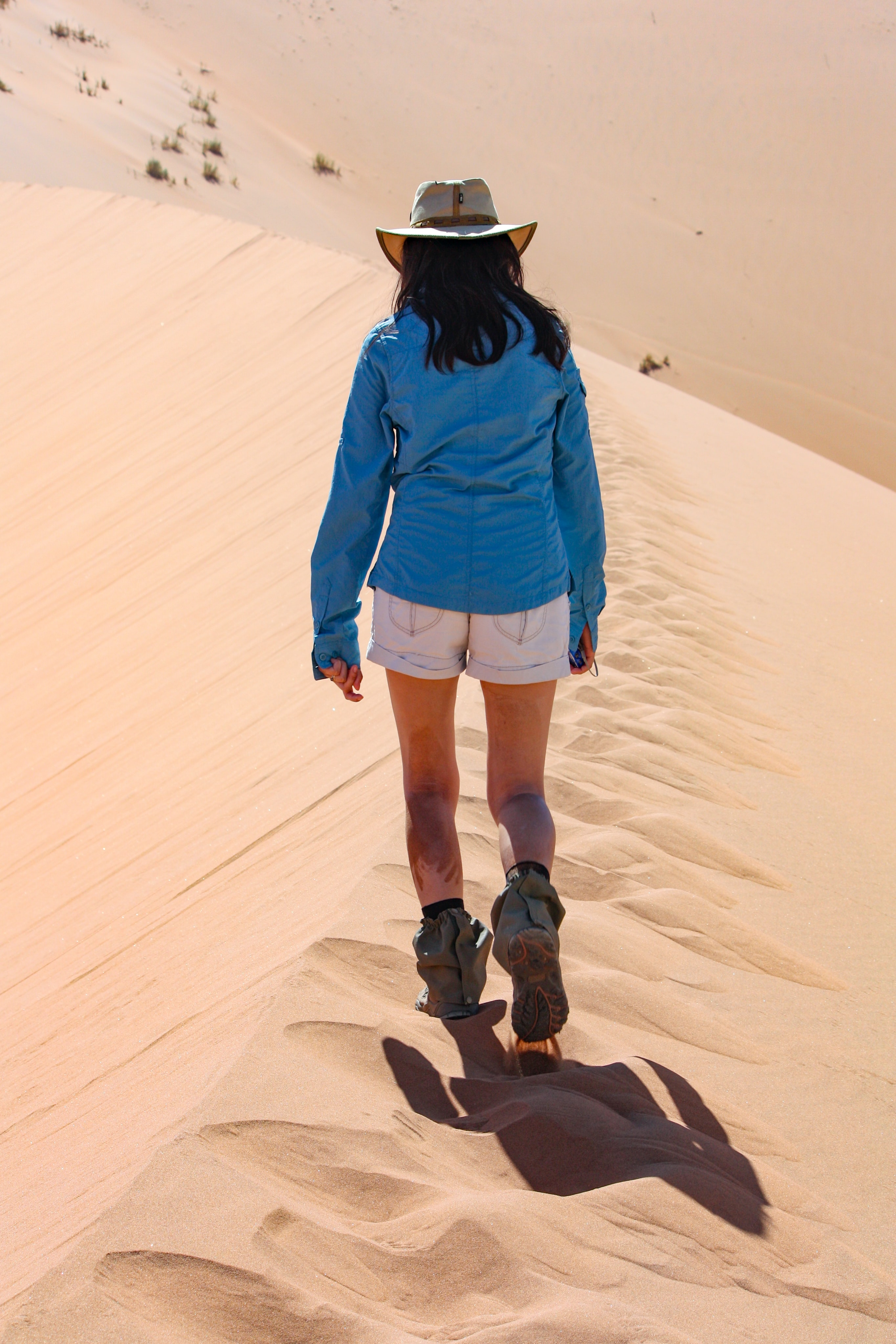woman walking on dessert during daytime