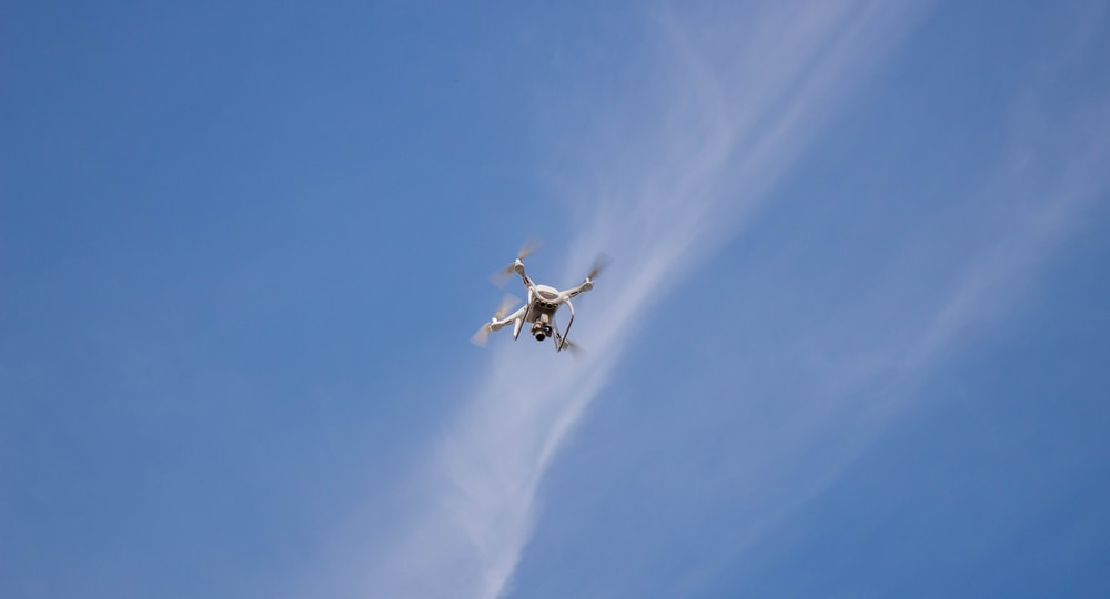 low-angle photography of flying white quadcopter drone at daytime