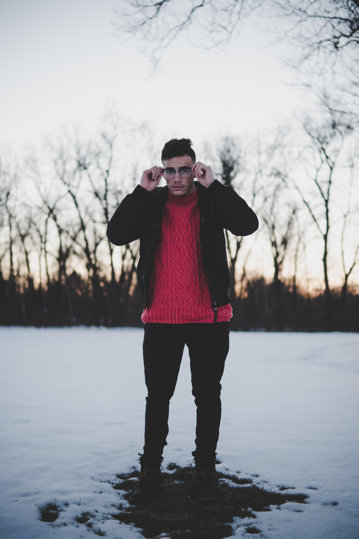 man standing holding his eyeglasses