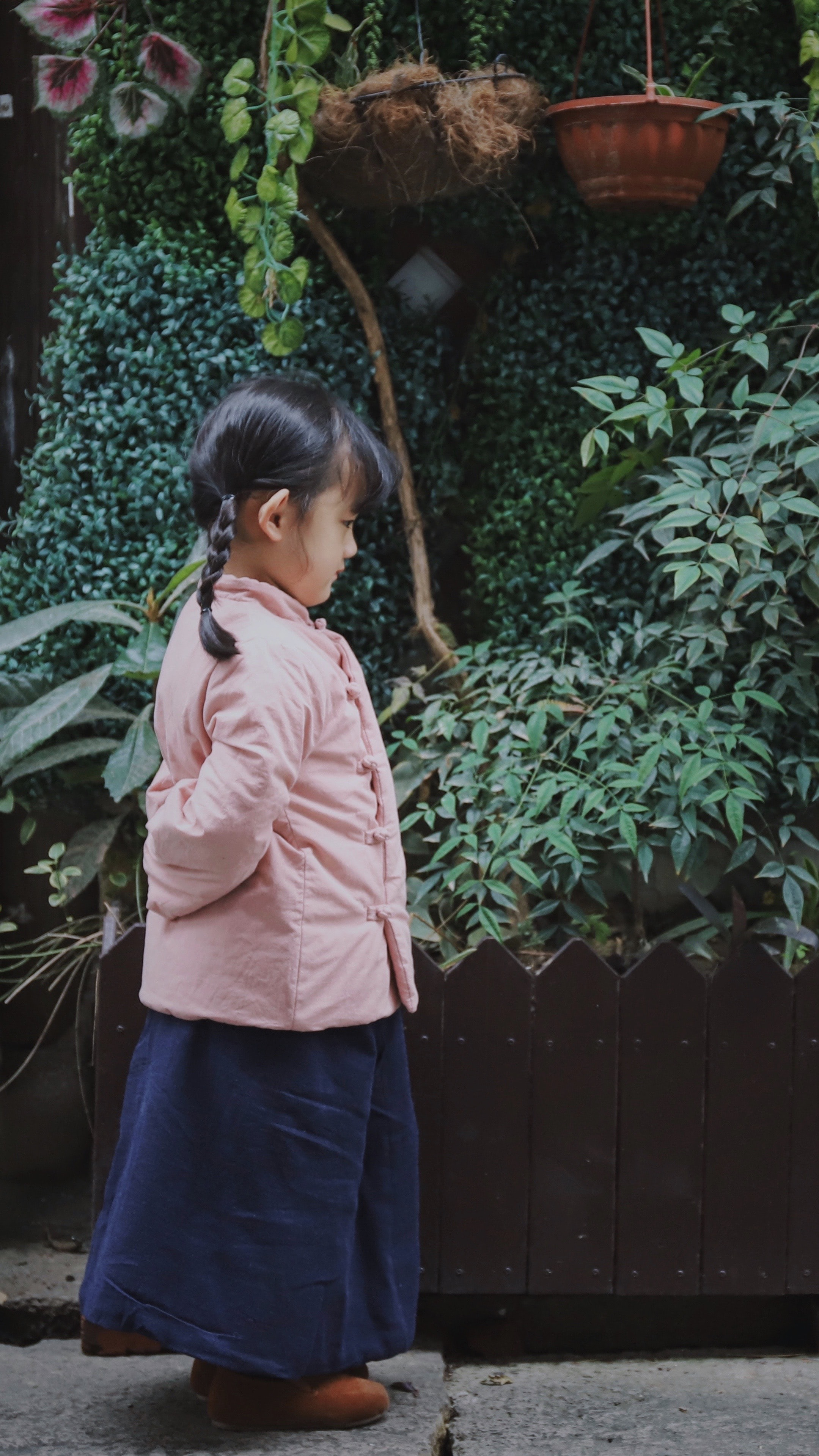 girl standing in front of garden