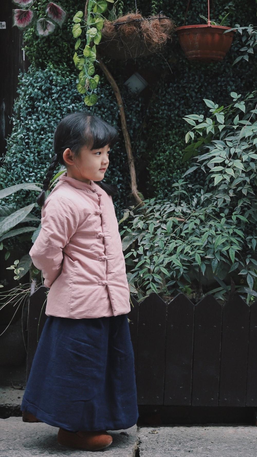 girl wearing pink jacket near plants