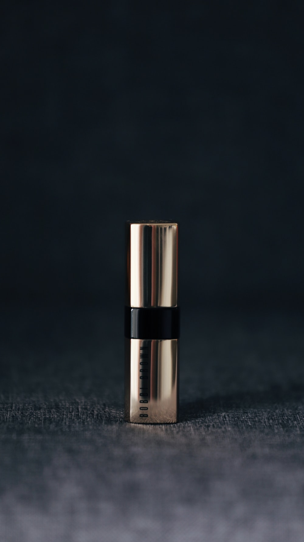 grey lipstick container in selective focus photography