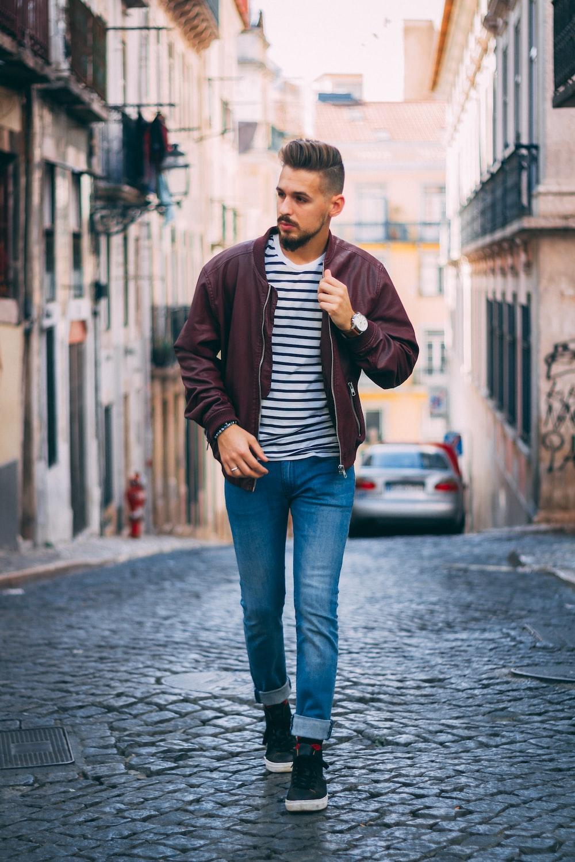 man in maroon zip-up jacket walking near building