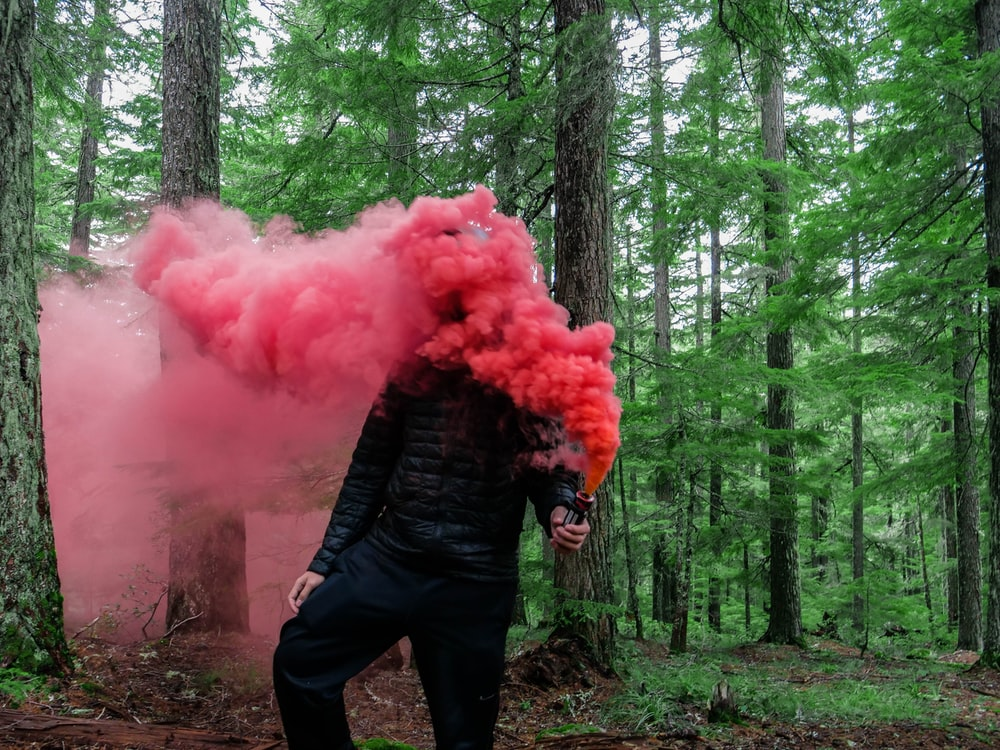 person holding smoke grenade with red color smoke