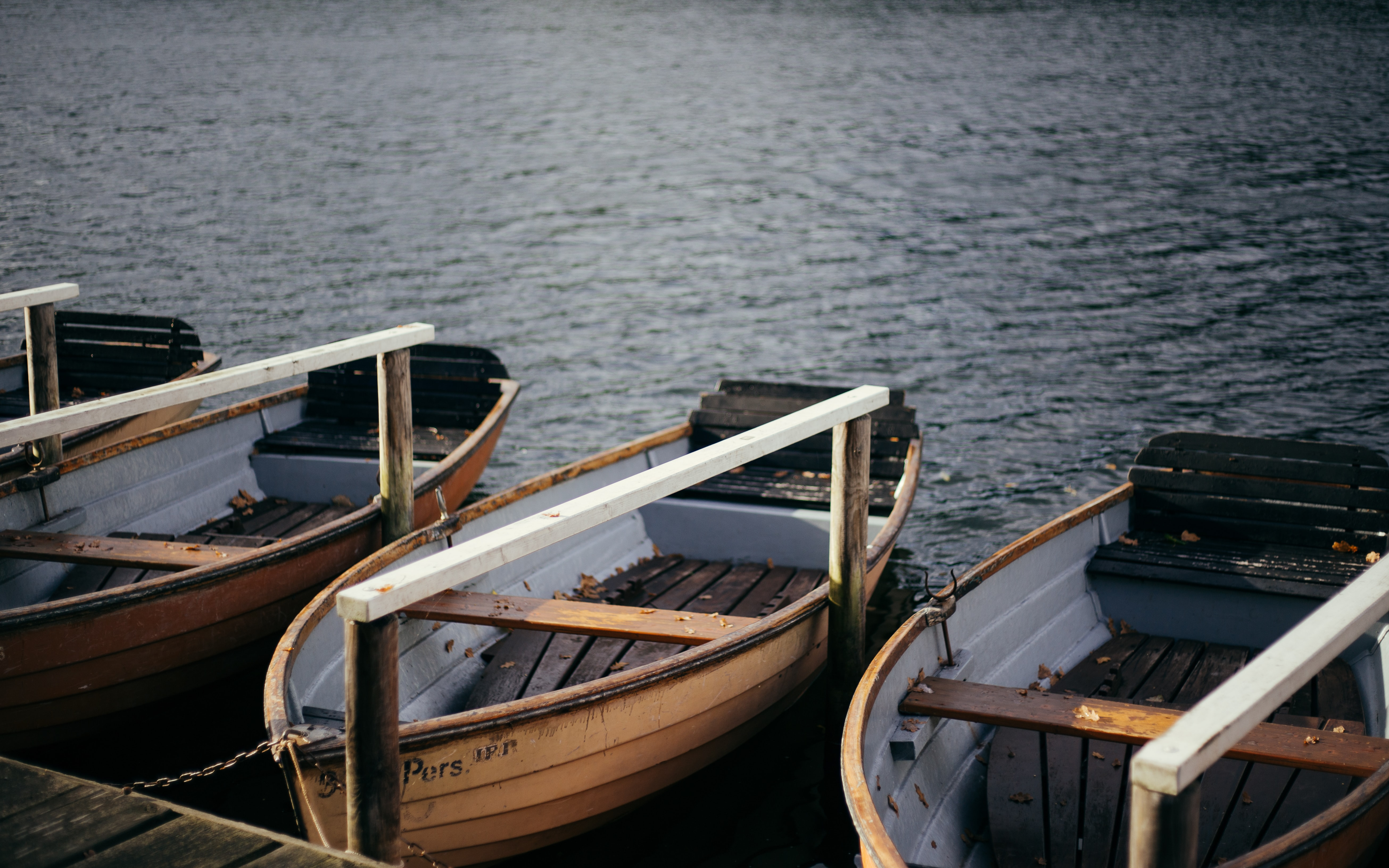 thee brown wooden boats beside dock with body of water during daytime