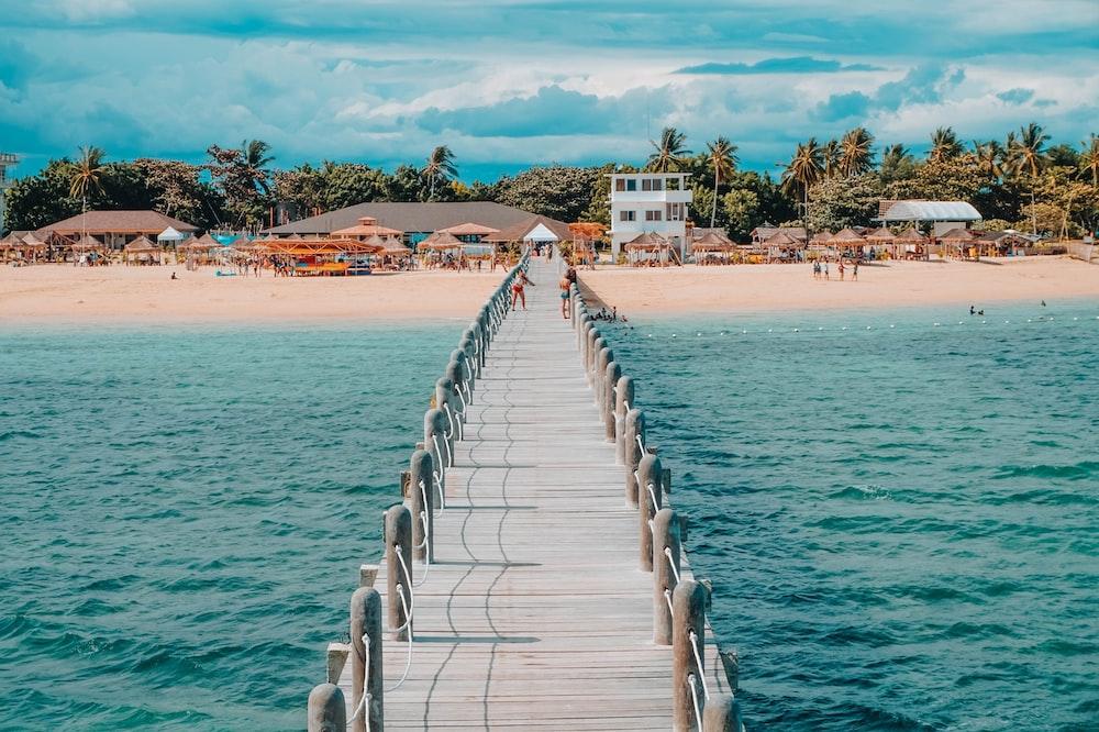 photo of brown wooden dock towards beach