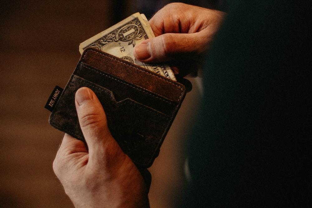 person getting 1 U.S. dollar banknote in wallet