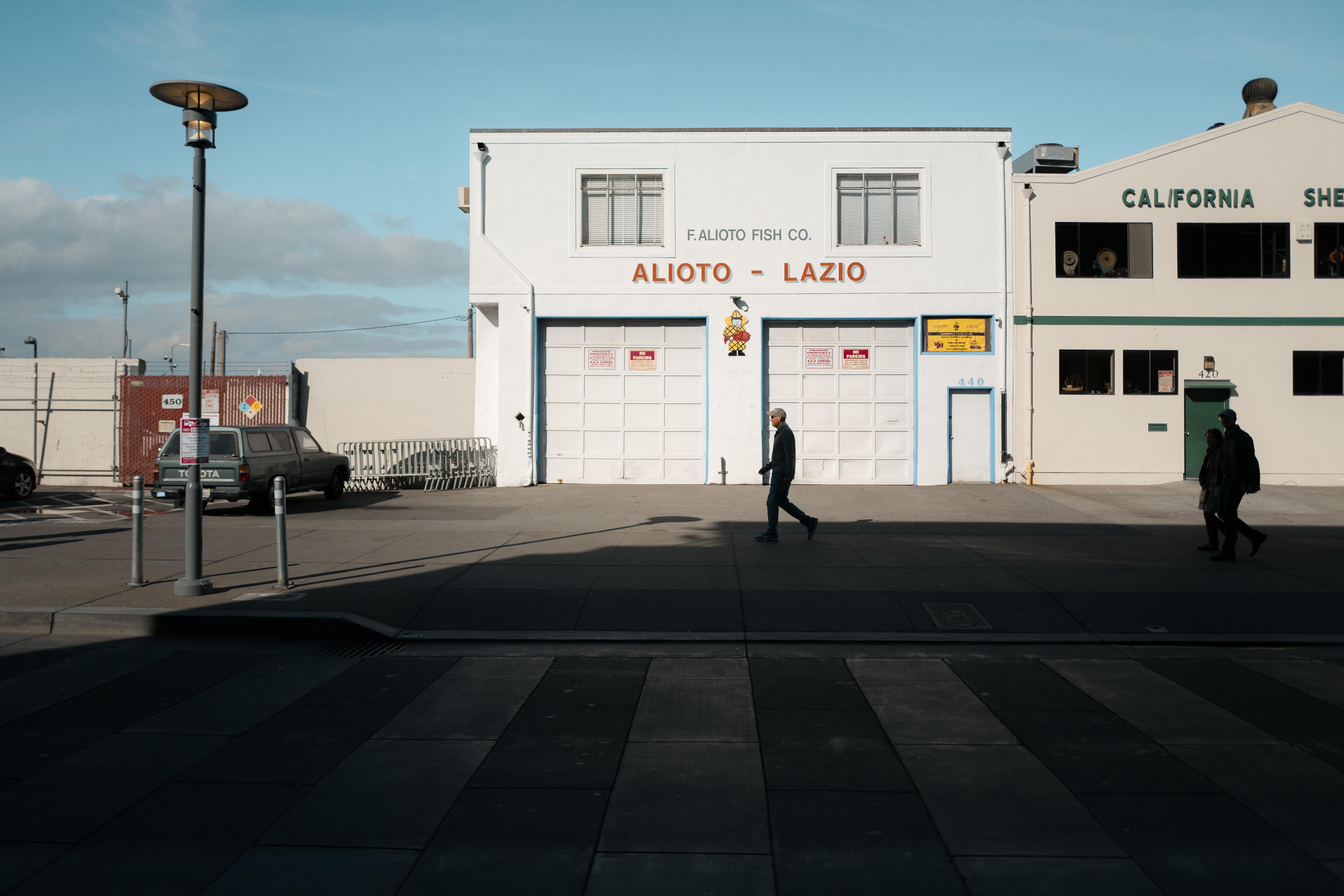 man walking in front of Alioto Lazio building