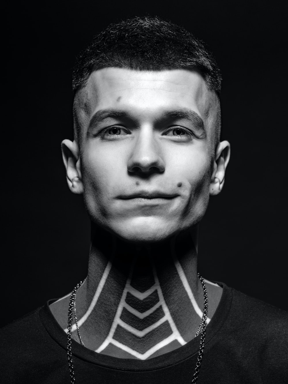 portrait photography of man with neck tattoos