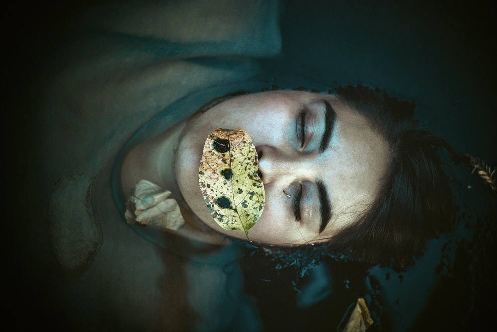 person with leaf on top of mouth