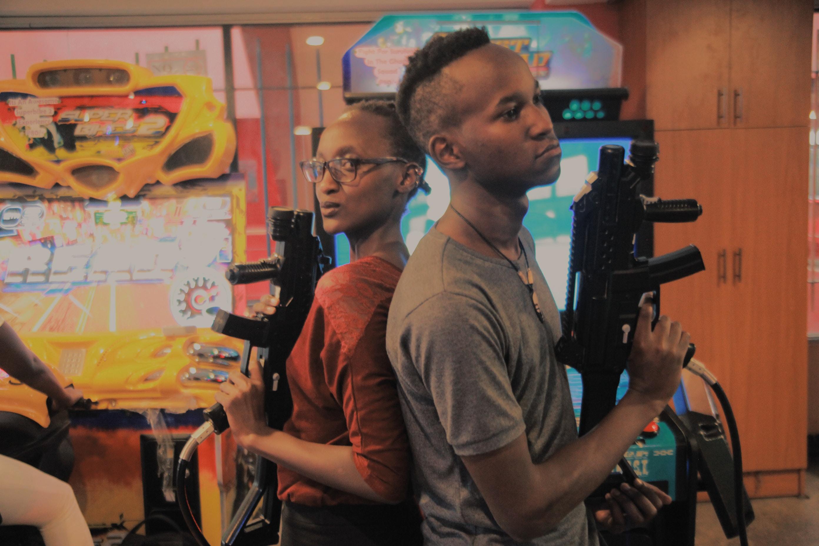 man and woman holding assault rifle arcade controller