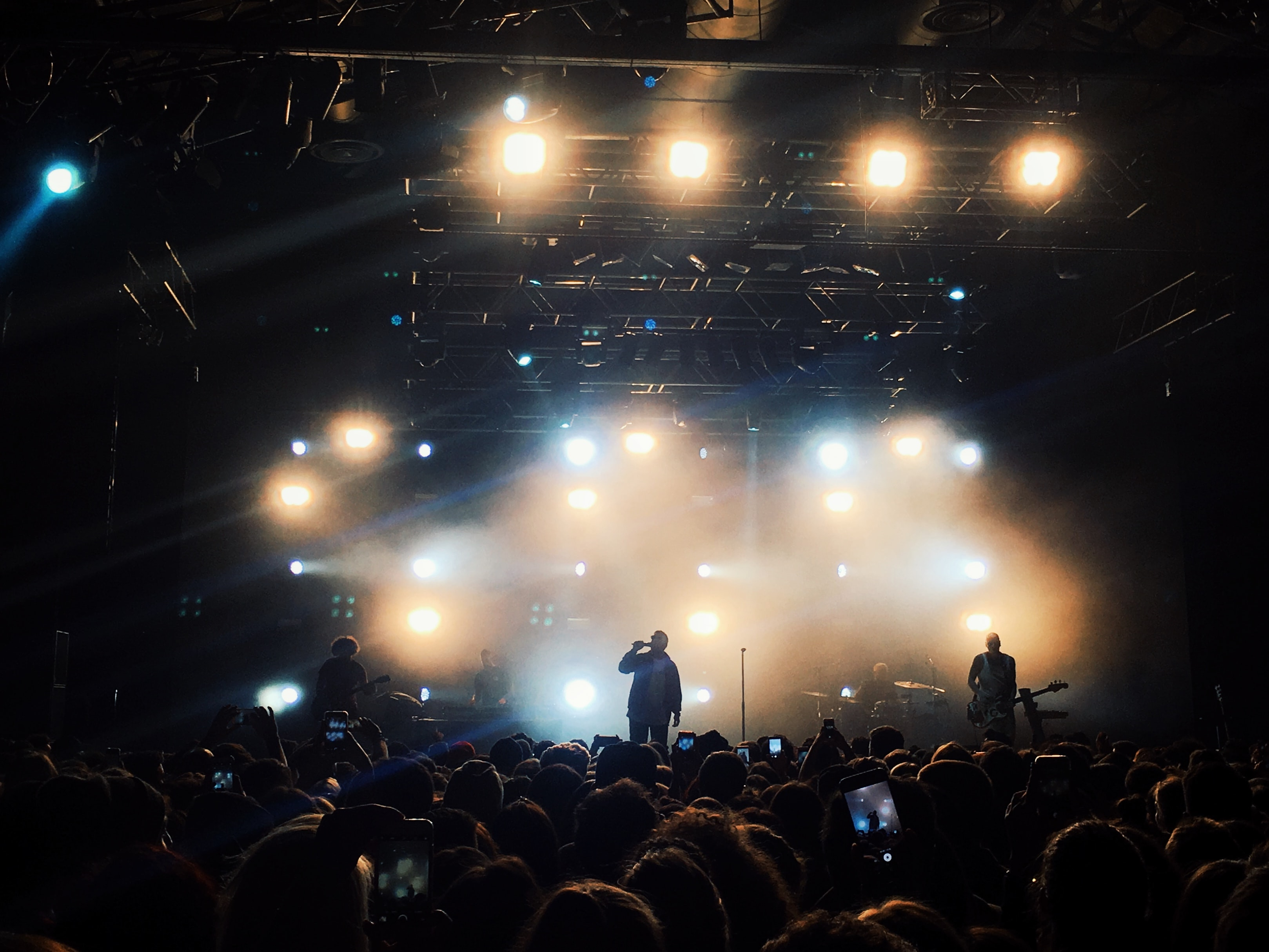 band performing on black stage surrounded by people