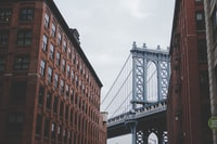 architectural photography of gray bridge and brown building