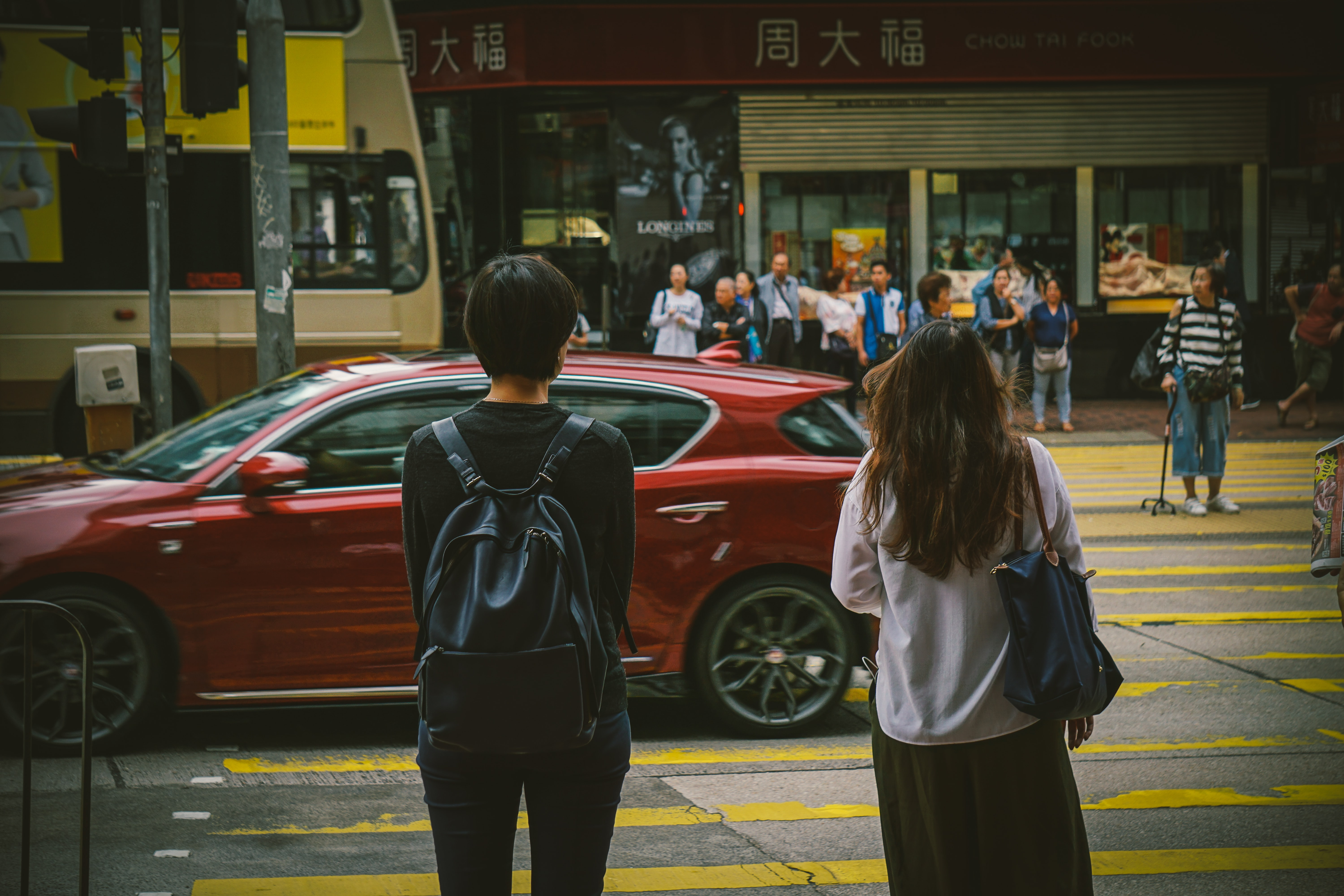 man and woman standing near red car