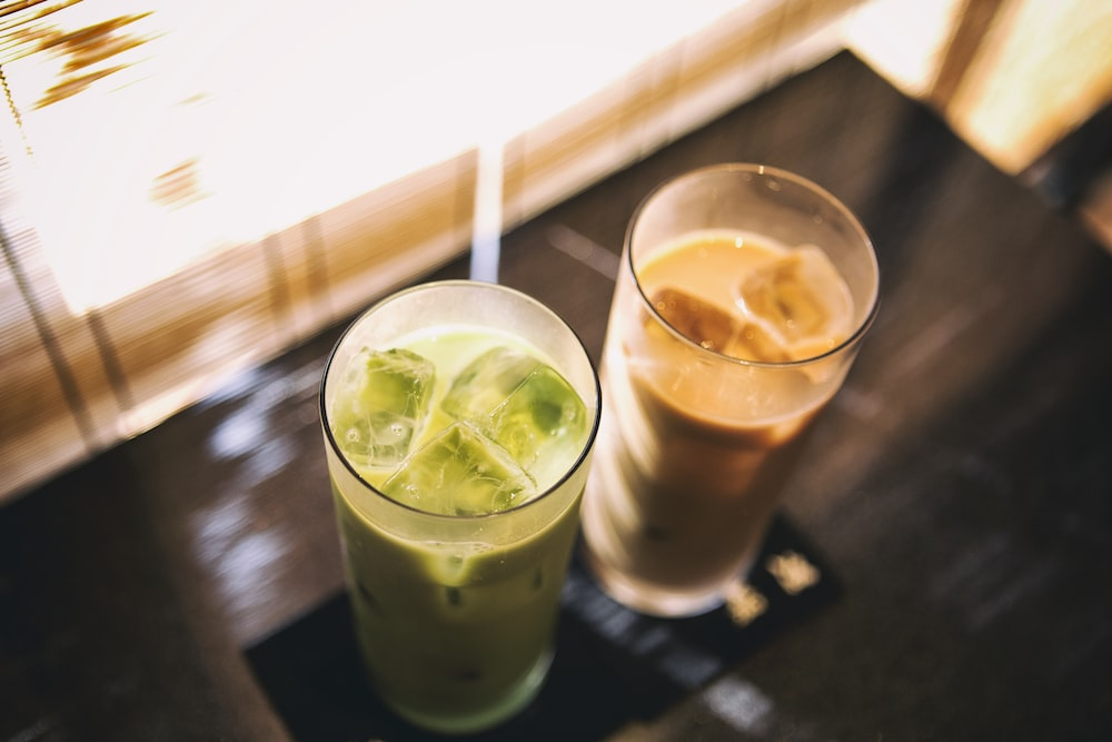 two glass cups with cold beverage inside
