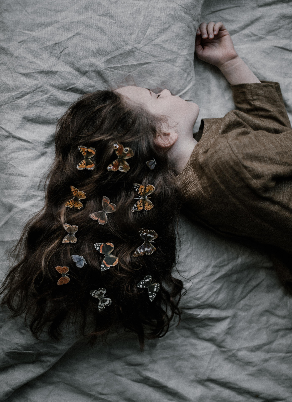 girl lying on gray bed sheet