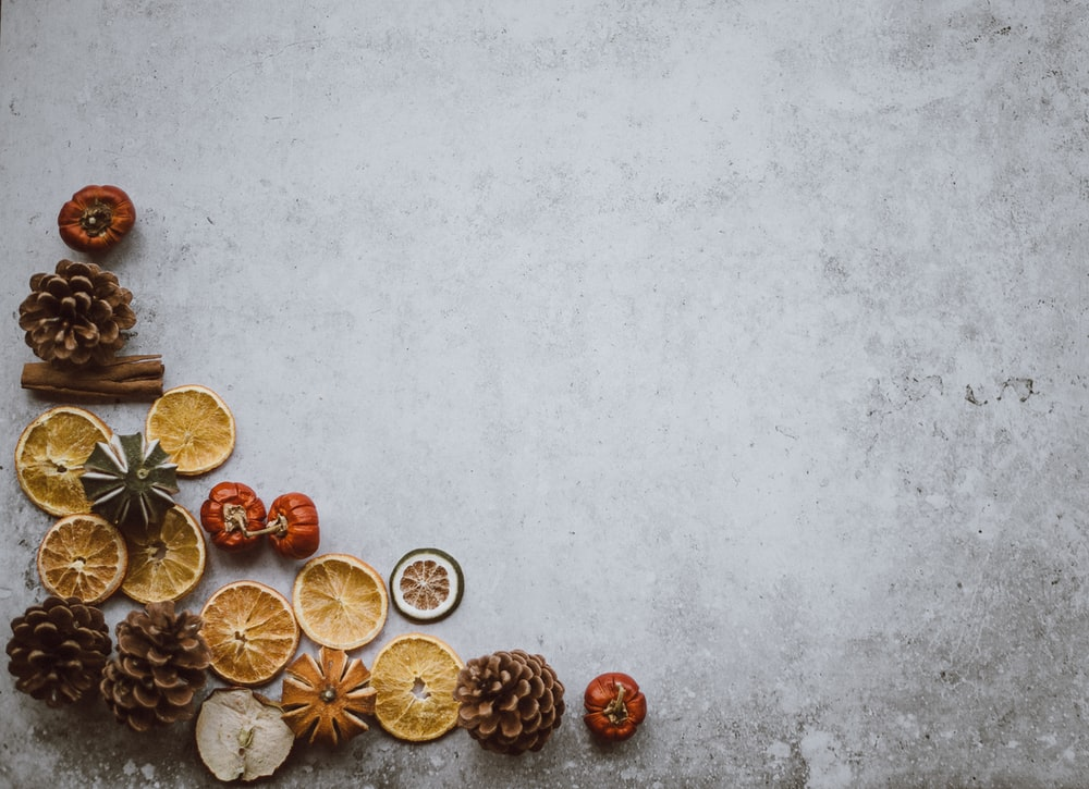 top view photo of brown pinecone and sliced fruit