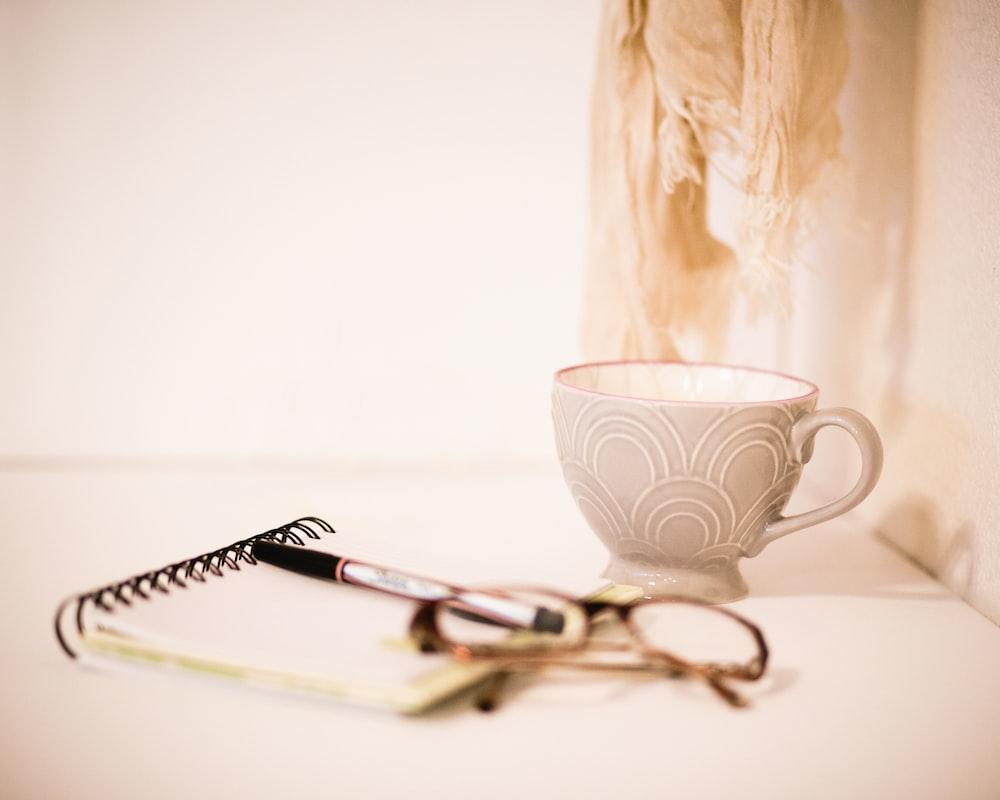 brown framed eyeglasses beside gray cup